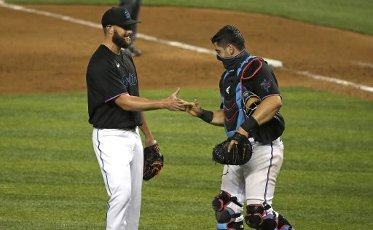 Miami Marlins pitcher Josh A. Smith, left, and catcher Francisco Cervelli celebrate after the final out in an 8-2 win against the Atlanta Braves at Marlins Park in Miami on Friday, Aug. 14, 2020. (David Santiago\/Miami Herald\/TNS