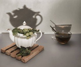 On the table in a teapot and a Cup of healthy herbal tea with sage.