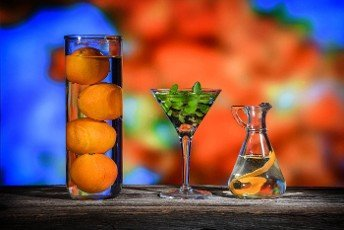 colorful still life of three glass containers with oranges,  zest and some green plant leaves