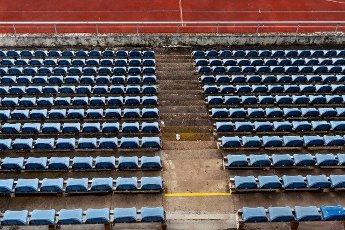 empty auditorium in athletic stadium,  rows of blue chairs.