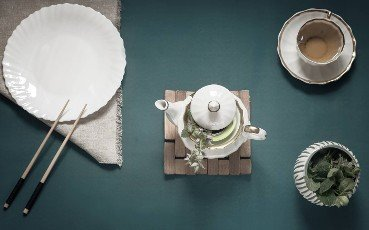 On the table is an empty plate,  chopsticks,  a teapot,  and a Cup of herbal tea. The pattern of Japanese cuisine. Top view with space to copy. Flat lay