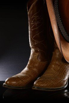 A pair of brown leather cowboy boots over a black background.