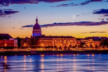 Moonrise and sunset lights over the Christuskirche in Mainz,  in the foreground the river rhine,  Germany