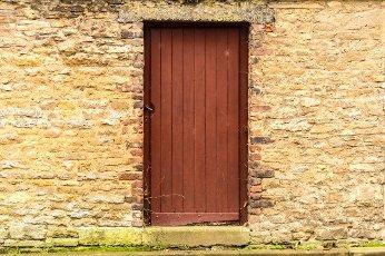 Old wooden door in the stone castle wall. Virton,  Belgium