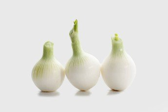 Detail of three onions on white background. Food.