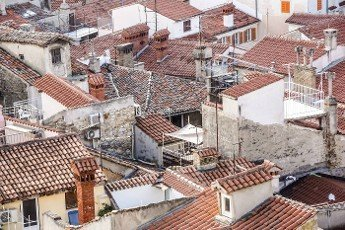 View of the tiled roof tops and scenic skyline of the Old Town of Dubrovnik,  taken from on top of its surrounding wall,  with the Adriatic Sea in the background.