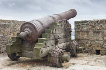 An old medieval fortress wall with an ancient cannon guarding its