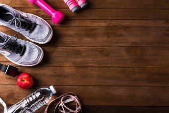 Top view of pair sports shoes,  apple,  jump rope and dumbbell on wood table,  Gray sneakers and accessories equipment in fitness GYM,  Healthy workout active lifestyle diet concept