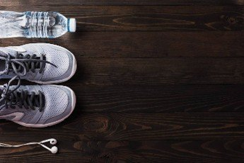 Top view of pair sports shoes,  headphones and water bottle on black wood table background,  Gray sneakers and accessories equipment in fitness GYM,  Healthy workout active lifestyle diet concept
