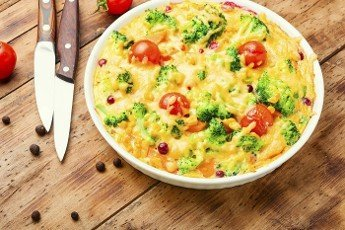 Vegetable casserole with broccoli, tomato and pumpkin on old wooden table.Frittata