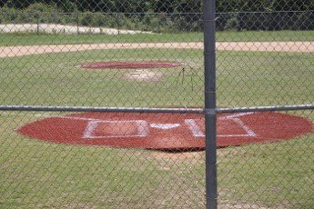 Home plate of an empty baseball field through a fence