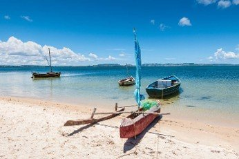 Malagasy outrigger pirogue with sail and boats on the white beach,  Madagascar