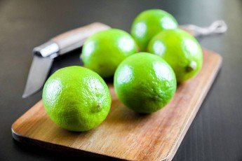 Lime and old traditional pocket knife on a wooden cutting board