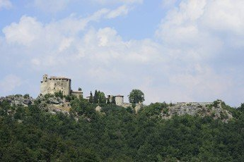 view of medieval fortification above a steep hill that defends the south side of the valley,  shot in bright summer light..