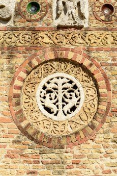 detail of round decoration on exterior wall of nartex at ancient Romanesque abbey,  shot in bright spring sun light at Pomposa,  Ferrara,   Italy.