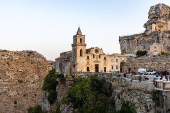 Matera,  Italy - September 17,  2019: View at Church of San Pietro caveoso and on the top of the hill of Church of Saint Mary of Idris in Matera,  Basilicata,  Italy