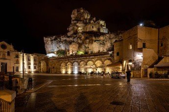Matera,  Italy - September 19,  2019: Night view at Church of San Pietro caveoso and on the top of the hill of Church of Saint Mary of Idris in Matera,  Basilicata,  Italy