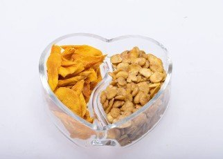 Roasted and salted fava beans and dried mango slices for a healthy vegan and vegetarian diet snack. High in protein,  vitamins,  dietary fibre and nutrients