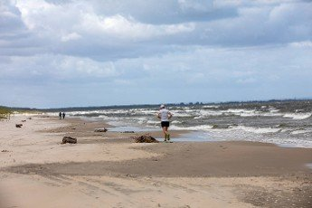 Stegna,  Poland - September 10,  2020: Man is running along the beach in Stegna. Poland