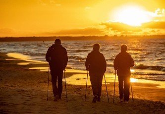 Stegna,  Poland - September 7,  2020: Active and healthy lifestyle. Nordic walking on a sandy beach sea shore