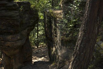 ground path between rock formation made from sandstones inside of a forest during summer season in piekielko nature reserve in Poland