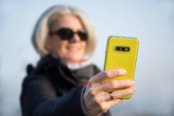 Elegant woman using yellow smartphone for selfie pic