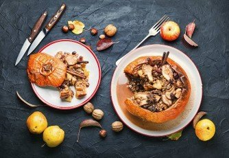 Pumpkin stuffed with granola and dried fruits on old wooden table