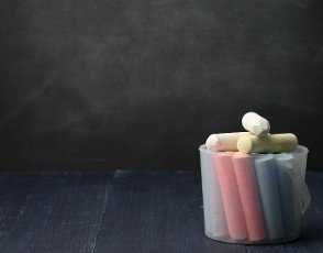 plastic bucket with colorful chalk on empty black chalk board background,  back to school,  copy space