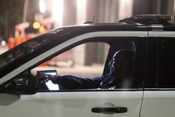 March 31, 2020 - Houston, Texas USA: Houston After Dark - Houston Police Sat. Hayes sits in his squad car monitoring a park in downtown Houston after midnight during the outbreak of Covid-19, March 31, 2020 (F. Carter Smith/Polaris)