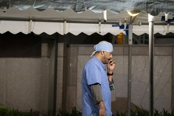 March 31, 2020 - Houston, Texas USA: Houston After Dark - A medical professional takes a phone call break during a walk outside the MD Anderson Cancer Center in Houston at 1am during the outbreak of Covid-19, March 31, 2020 (F. Carter Smith/Polaris)