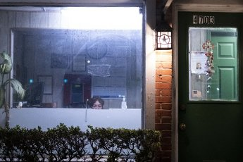 March 30, 2020 - Houston, Texas USA: Houston After Dark - The night clerk at the Admiral Motel sits behind bulletproof glass near midnight during the outbreak of Covid-19, March 31, 2020 (F. Carter Smith/Polaris)