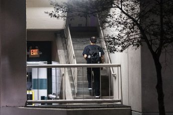 March 31, 2020 - Houston, Texas USA: Houston After Dark - A medical professional, still wearing his protective mask, walks to his car in the parking lot next to CHI St. Luke