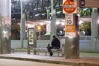 March 31, 2020 - Houston, Texas USA: Houston After Dark - A man sits and waits at the Metro Bus station in downtown Houston after midnight during the outbreak of Covid-19, March 31, 2020 (F. Carter Smith/Polaris)