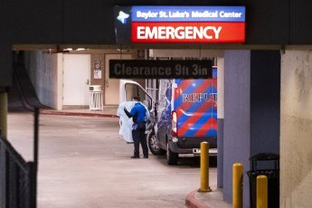 March 31, 2020 - Houston, Texas USA: Houston After Dark - An ambulance driver puts on his personal protective equipment (PPE) in the emergency room entrance at CHI St. Luke