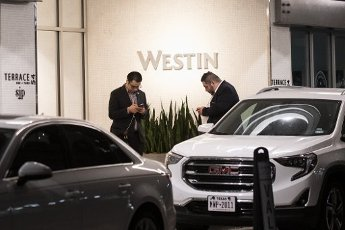 March 31, 2020 - Houston, Texas USA: Houston After Dark - Two hotel employees check their smartphones outside the entrance to the Westin Texas Medical Center Hotel after midnight during the outbreak of Covid-19, March 31, 2020 (F. Carter Smith/Polaris)