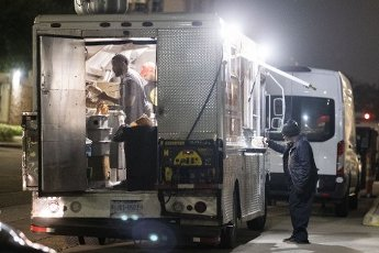 March 31, 2020 - Houston, Texas USA: Houston After Dark - A customer waits for his order to be prepared at the Happy Plate Express food truck next to the Harris County Sheriff