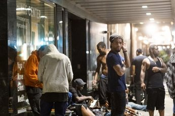 March 31, 2020 - Houston, Texas USA: Houston After Dark - Members of the homeless population gathered in front of the Hines Center after midnight are not practicing social distancing during the outbreak of Covid-19, March 31, 2020 (F. Carter Smith/Polaris)