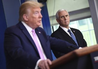 April 10, 2020 - Washington, DC, United States: President Donald Trump speaks as Vice President Mike Pence listens at a Coronavirus briefing at the White House. With the U.S. death toll from the coronavirus pandemic expected to peak over the weekend, most of the country will be firmly under stay-at-home orders on Easter Sunday. (Polaris)