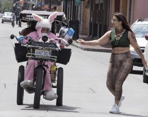April 10, 2020 - New Orleans, Louisiana USA: A passerby gives a tip to Marie Francois, also known as the âQueen of Bourbon Streetâ on a nearly deserted Bourbon Street on Good Friday in the midst of the Coronavirus crisis. The state of Louisiana is currently reporting 19,253 cases with 755 deaths, and 2,054 patients currently being treated in hospitals. New Orleans leads the state with 5,416 cases and 225 deaths. Francois tested positive for the Coronavirus in March. A local celebrity, Francois is known for her buggy, costumes and loud music. She has recovered and hit the streets again, with the proper protection. She doubts she will qualify for government relief. She told Doug MacCash at New Orleans Advocate: âI donât think the government is going to give street performers a stimulus check.â (David Rae Morris / Polaris)