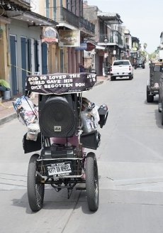 April 10, 2020 - New Orleans, Louisiana USA: Marie Francois, also known as the âQueen of Bourbon Streetâ rides up a nearly deserted Bourbon Street on Good Friday in the midst of the Coronavirus crisis. The state of Louisiana is currently reporting 19,253 cases with 755 deaths, and 2,054 patients currently being treated in hospitals. New Orleans leads the state with 5,416 cases and 225 deaths. Francois tested positive for the Coronavirus in March. A local celebrity, Francois is known for her buggy, costumes and loud music. She has recovered and hit the streets again, with the proper protection. She doubts she will qualify for government relief. She told Doug MacCash at New Orleans Advocate: âI donât think the government is going to give street performers a stimulus check.â (David Rae Morris / Polaris)