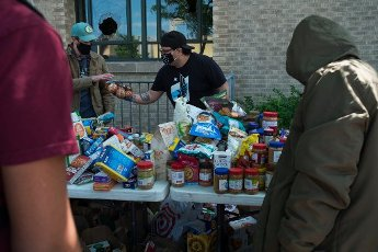 May, 30, 2020 - Minneapolis, Minnesota, United States: Volunteers pass of food donations to community members in front of Midtown Global Market on Lake Street in Minneapolis. Hundreds of volunteers showed up around Lake Street to clean up following riots the night before. (Brooklynn Kascel\/Polaris)