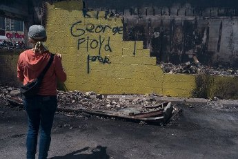 May, 30, 2020 - Minneapolis, Minnesota, United States: A bystander observes damage to Lake Street following another night of protesting and vandalism. Hundreds of volunteers showed up around East Lake Street to clean up following riots the night before. (Brooklynn Kascel\/Polaris)