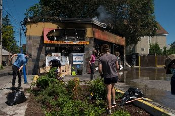 May, 30, 2020 - Minneapolis, Minnesota, United States: Volunteers clean up fire damage to a gas station on Lake Street following another night of protesting and vandalism. Hundreds of volunteers showed up around East Lake Street to clean up following riots the night before. (Brooklynn Kascel\/Polaris)