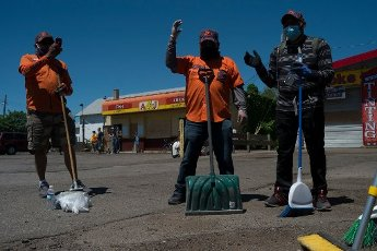 May, 30, 2020 - Minneapolis, Minnesota, United States: Members of the community pray in a group in front of A and J\'s Fish and Chicken on Lake Street in Minneapolis. Hundreds of volunteers showed up around East Lake Street on Saturday morning to clean up following riots the night before. (Brooklynn Kascel\/Polaris)