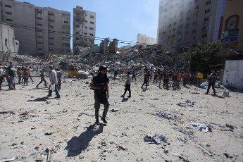 Palestinians inspect the rubbles of the Jalaa Tower after it is destroyed in an Israeli airstrike in Gaza city on May 15, 2021 Israel\'s air force targeted the 13-floor Jalaa Tower housing Qatar-based Al-Jazeera television and the Associated Press news agency.. Israeli air strikes pounded the Gaza Strip, killing 10 members of an extended family and demolishing a key media building, while Palestinian militants launched rockets in return amid violence in the West Bank. (Naaman Omar\/APAImages\/Polaris