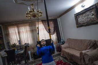 Iranian performer, Mohsen Shahed, exercises at an apartment in southern Tehran that uses as a place for home quarantine, due to the new coronavirus (COVID-19) outbreaking in Iran on April 10, 2020. Mohsen moved his bodybuilding devices to his father