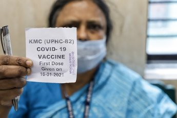 A woman health worker shows her first vaccination receipt as she has been vaccinated with Covishield coronavirus vaccine developed by Oxford University & AstraZeneka Plc & produced by Serum Institute of India, at Mayor\'s Health Clinic, Chetla on the first day of nationwide vaccination drive against covid-19 launched by prime minister of India Narendra Modi. (Photo by Jit Chattopadhyay \/ SOPA Images\/Sipa USA
