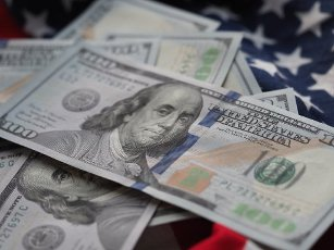 In this photo illustration, US 100 dollar bills seen on an American flag. (Photo by Igor Golovniov \/ SOPA Images\/Sipa USA