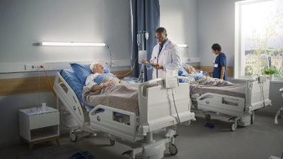 Doctor talking with elderly patient on hospital ward