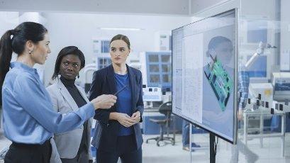 Team of engineers looking at a digital whiteboard